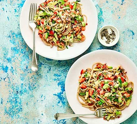Two plates serving linguine with avocado, tomato & lime