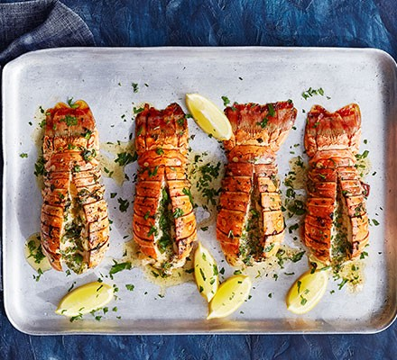 Grilled lobster tails with lemon & herb butter served on a baking tray