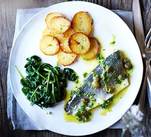 A plate of sea bass with spinach and potatoes