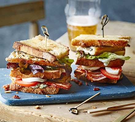 Two mackerel club sandwiches served on a board