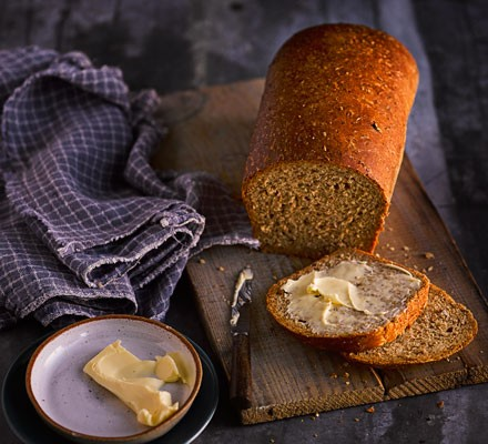 Loaf of Irish malted bread on a wooden board with butter