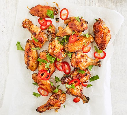 Mango & lime chicken wings served on a baking sheet of paper
