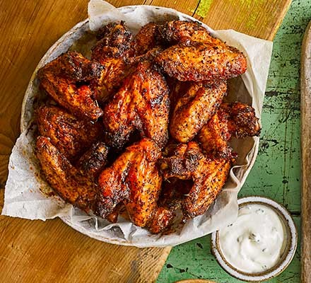 Maple-glazed hot wings in a serving dish with dip