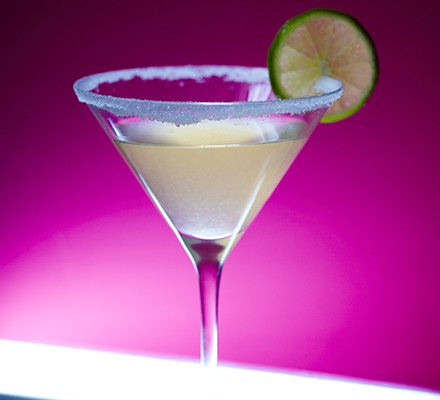 Margarita in a cocktail glass with a slice of lime, on a pink background