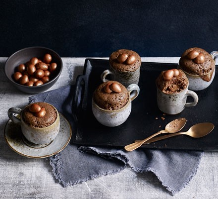 Chocolate mug cakes with chocolate eggs and spoons