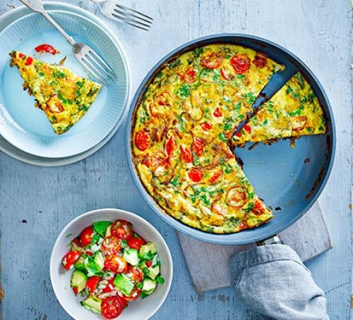 A frittata in a frying pan with avocado salsa in a bowl