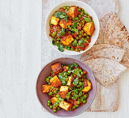 Two bowls filled with matar paneer with some flatbreads alongside