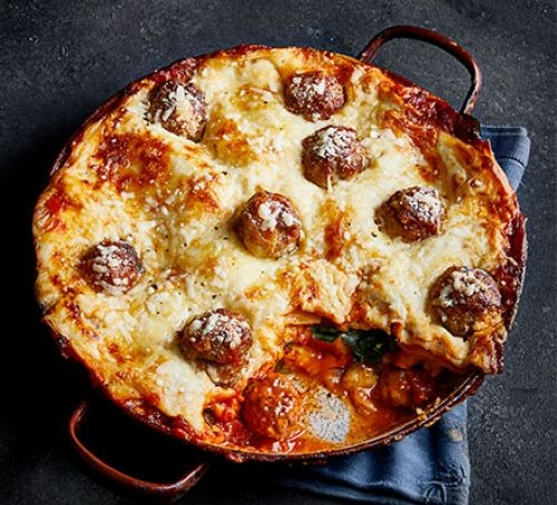 Meatball lasagne topped with melted cheese with a slice cut out
