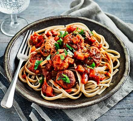 A plate serving slow cooker meatballs with spaghetti