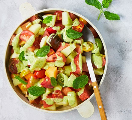 Salad of melon & tomatoes with mint & elderflower dressing served in a salad bowl
