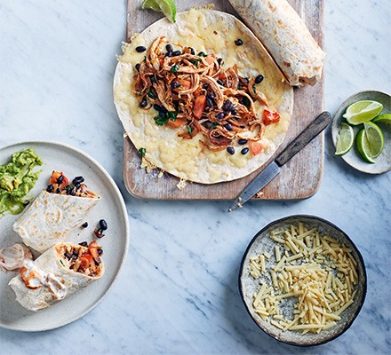 Mexican chicken & black bean wraps served on a chopping board