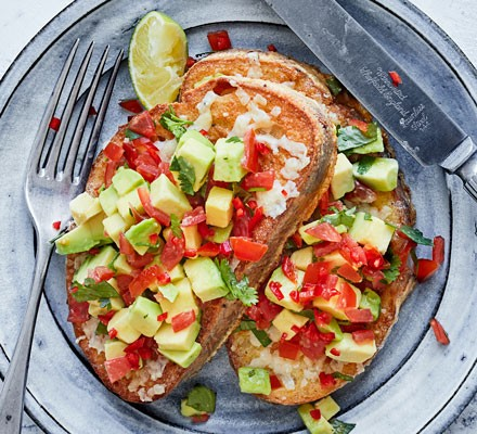 Toast with avocado and tomato on plate with cutlery