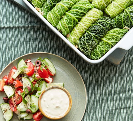 A baking dish of cabbage rolls with salad