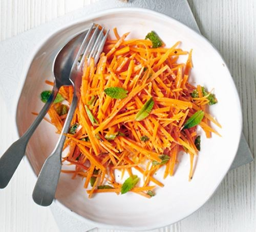 Grated carrots and herbs on a plate, with cutlery