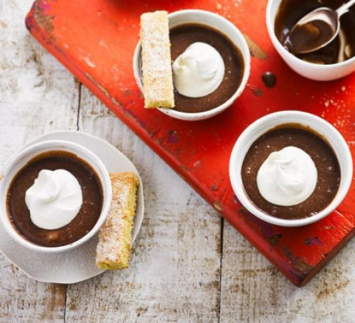 Three milk chocolate pots topped with cream and shortbread sticks