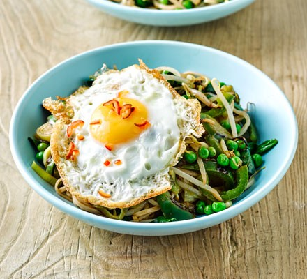 A bowl of wholemeal noodles with vegetables and fried eggs