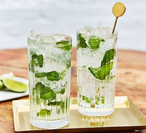 Mojitos in glasses with mint and stirrer