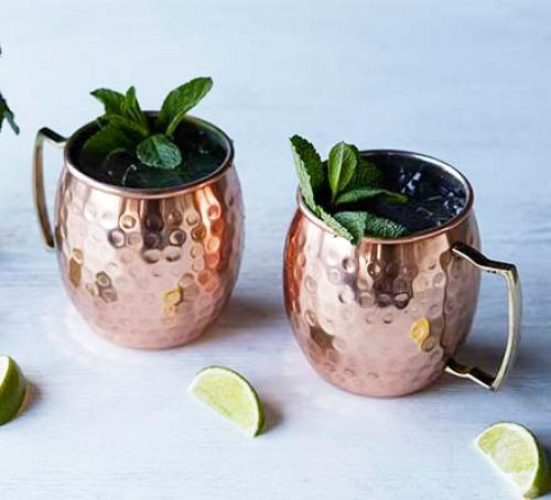 A Moscow mule served in copper mugs and ganished with mint leaves