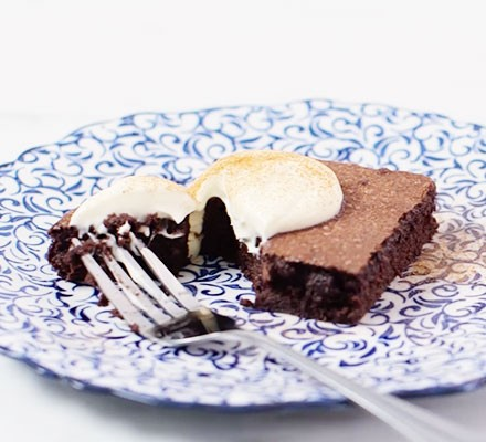 A mulled wine brownie on a plate with a dollop of cream on top