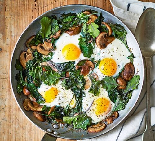 Four fried eggs with mushrooms in a pan