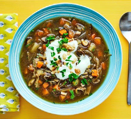 Mushroom and potato soup with carrots in bowl with spoon
