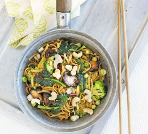 Mushroom & broccoli noodles in a pan with chop sticks at the side