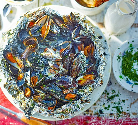 A bowl of barbecued mussels garnished with herbs
