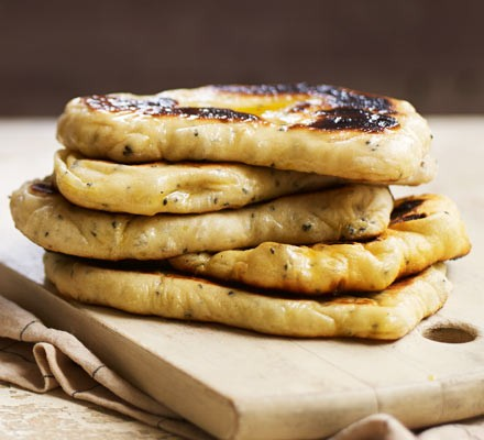 Warm naan bread stacked in a pile