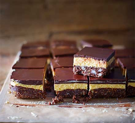 Squares of nanaimo bars on a chopping board