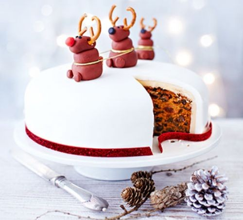 Christmas cake with Rudolph decorations on a cake stand with a slice missing, next to pine cones