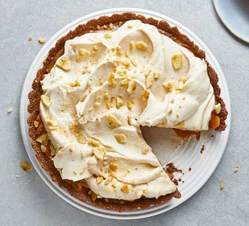 Banoffee pie topped with cream frosting and bananas