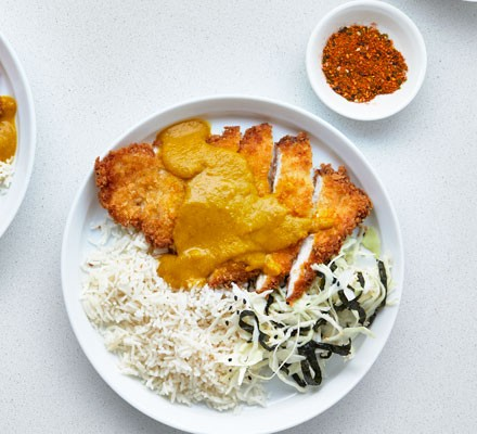Next level chicken katsu curry on a plate with rice, cabbage and seaweed