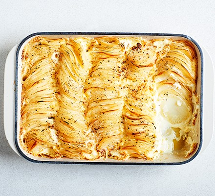Layers of Dauphinoise potatoes in a casserole dish