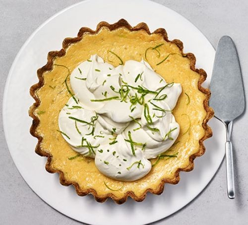 Key lime pie topped with cream and grated lime