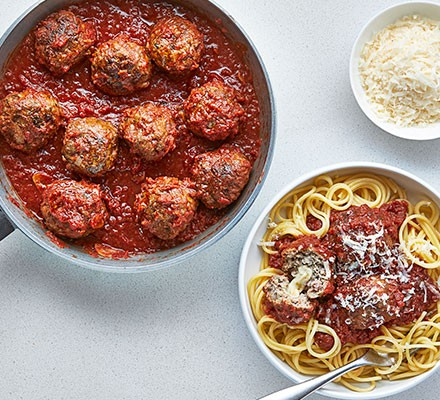 Next level meatballs served in a pan, with spaghetti alongside