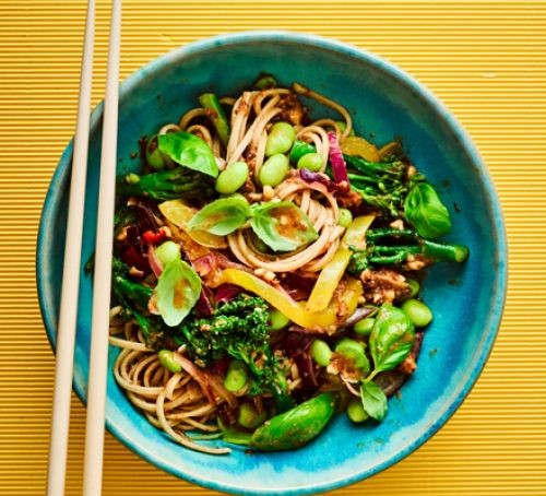 Sticky noodles and edamame beans in a blue bowl with chopsticks