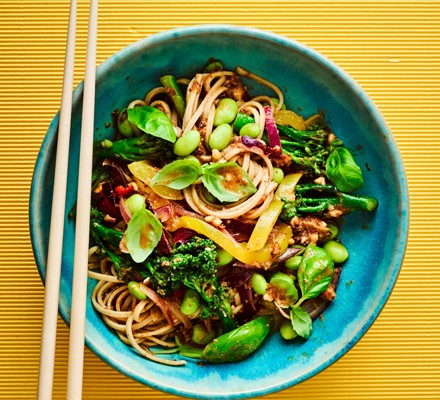 Noodles with green veg in blue bowl with chopsticks on yellow background