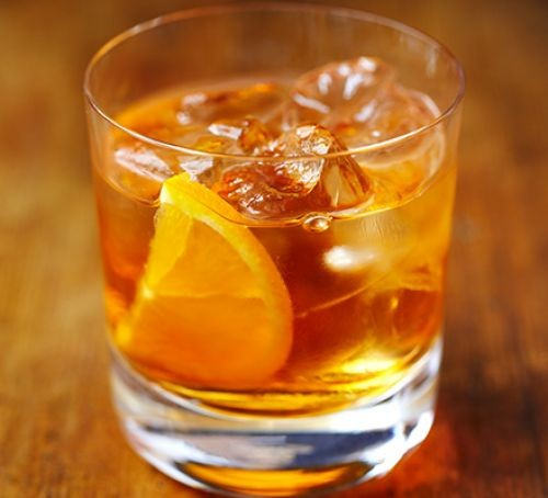 Old fashioned whisky cocktail in a glass with orange slice