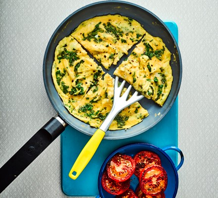 Omelette cut into quarters in pan with spatula and tomatoes