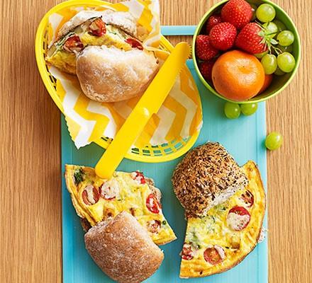 Omelette in a bun served on a chopping board alongside fruit