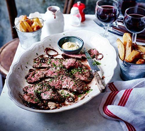 Onglet steak on plate next to pots of potato chips
