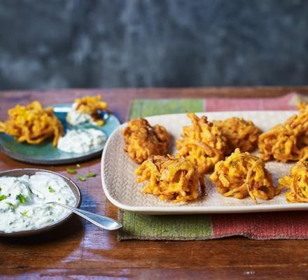 Onion bhajis on a tray with a bowl of raita