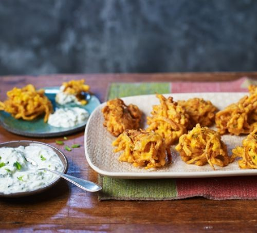 Onion bhajis on a plate with raita in a bowl