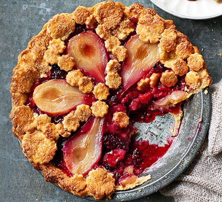 A pie dish serving a pear & berry pie
