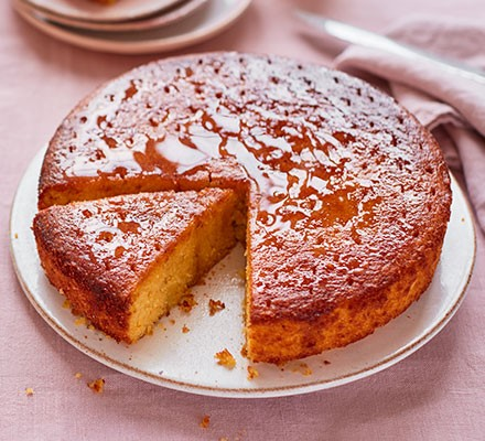 Orange olive oil cake served on a plate with a slice cut out