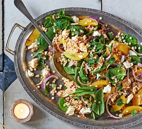Oval bowl of giant couscous with orange segments, feta and spinach