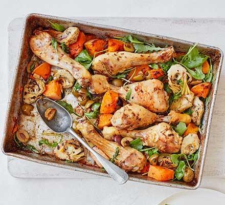 A casserole dish serving oregano chicken & squash traybake
