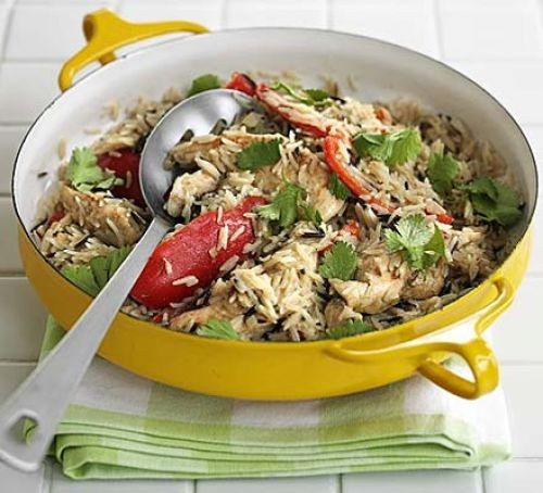 Oven-baked Thai chicken with rice and peppers in a serving dish with a spoon