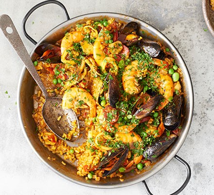 Paella with prawns and mussels served in a pan