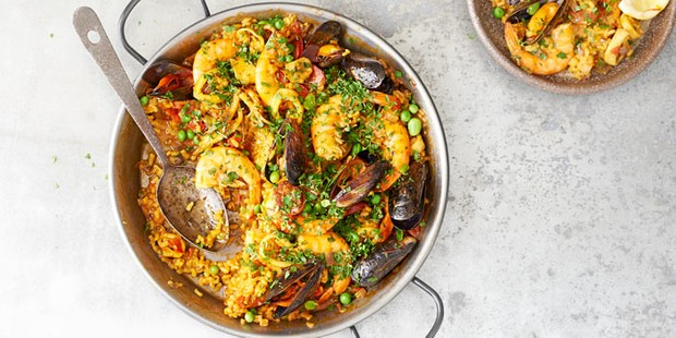 Paella with seafood and spoon in bowl